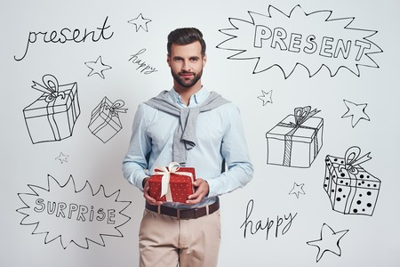 Surprise! Charming bearded man is holding a gift box and smiling while standing against grey background with different doodle illustrations on it. Birthday concept