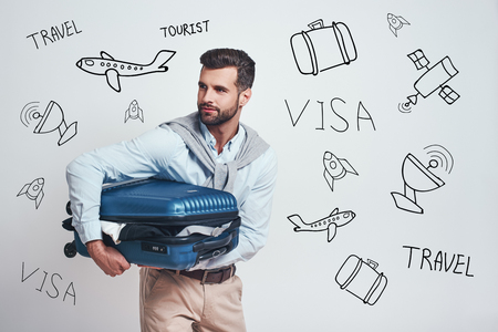 Ready to travel! Smiling handsome man is holding his suitcase full of clothes while standing against grey background with different travel doodles on it. Travel concept. Artwork