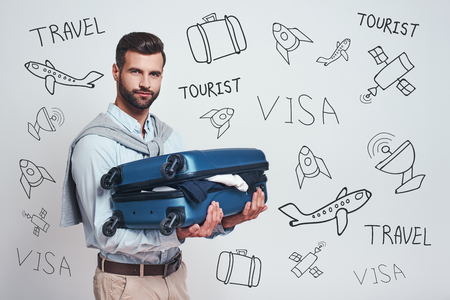 Business trip. Excited and handsome man is holding his suitcase and looking at camera while standing against grey background with different travel doodles on it. Travel concept