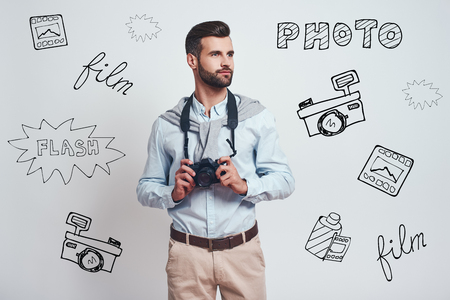 Confident photographer. Handsome young man in casual clothes is holding camera and looking away while standing against grey background with different doodle illustrations on it. Hobby concept