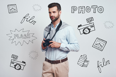 Creative man. Charming young man is holding digital camera and looking away while standing against grey background with different doodle illustrations on it. Hobby concept.