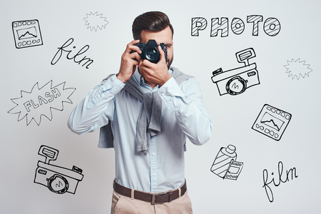 Do what you love. Young bearded man in blue shirt taking a picture on digital camera while standing against grey background with different doodle illustrations on it. Hobby. Art work Stock fotó