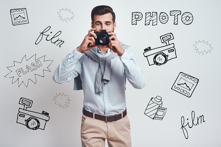 Smile! Close up photo of handsome male photographer in casual clothes making a photo on digital camera while standing against grey background with different doodle illustrations on it. Hobby concept Stock fotó