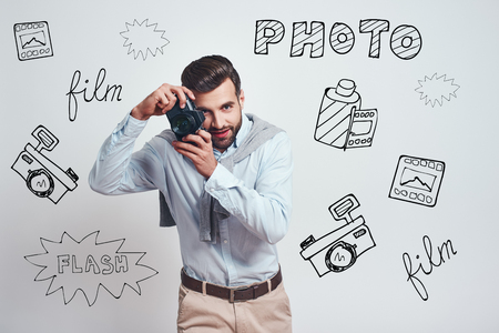 Nice shot. Attractive young man in casual wear making a photo or shooting video on digital camera while standing against grey background with different doodle illustrations on it. Hobby concept
