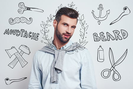 I don't like this hairstyle. Handsome young man in casual wear making doubt emotion while standing against grey background with doodles on the theme of barber shop. Doubt concept. Men beauty. Hair care Foto de archivo - 126116799