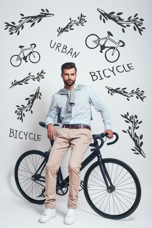 Avoiding traffic. Full length of good looking man with beard leaning on his bicycle against grey background with hand drawn doodles on it. Urban style. City life