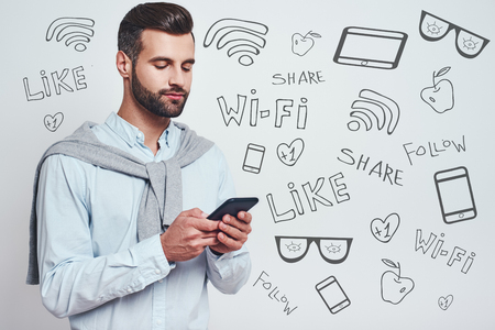 Surfing the net. Young bearded man in casual wear using his smart phone while standing against grey background with different doodle illustrations on it. Social media concept. Digital concept. Close-up Stock fotó