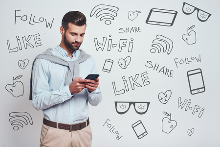 Social media concept. Handsome young man in casual wear using his smart phone while standing against grey background with different doodle illustrations on it. Modern technologies Stock fotó