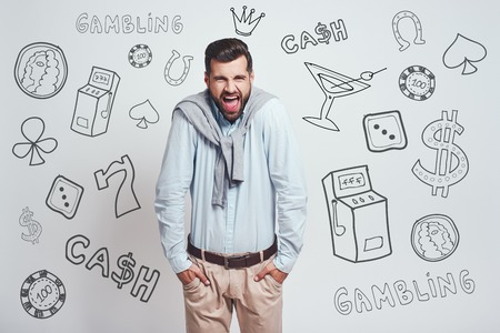 Bad luck. Angry young man keeping hands in his pockets and shouting while standing against grey background with different doodle illustrations on it. Gambling concept. Money. Human emotions