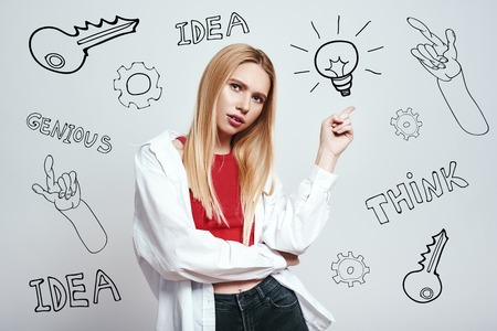 I have an idea! Pretty blonde woman in casual clothing pointing pointing at lightbulb while standing against grey background with hand drawn doodles on it