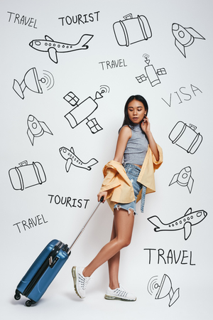 Ready for adventure! Full length of smiling beautiful asian woman carrieng her luggage while standing against grey background with doodles on the theme of travel.