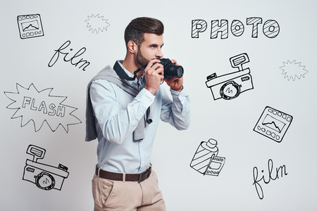 Ready to make a photo. Young attractive man is going to make a photoon digital camera while standing against grey background with different doodle illustrations on it. Hobby concept