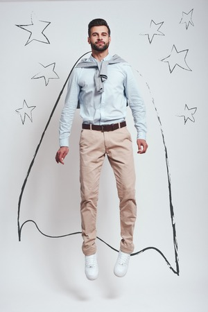 Superhero. Full length of confident bearded man wearing a drawn cape and jumping in studio against grey background with illustration of stars on it. Stock fotó