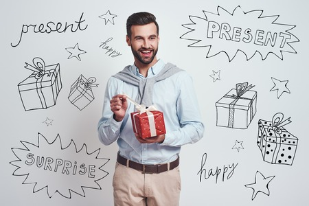 Its for me? Portrait of a young happy man opening red gift box and looking at camera with smile while standing against grey background with different doodle illustrations on it Banco de Imagens