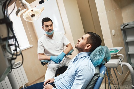 Excellence in dentistry with optimum care. Dentist in mask and latex gloves sitting near his patient in dental clinic
