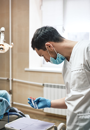 The experience you can count on. Dentist hold tools in his hand prepare to work in the cabinet.