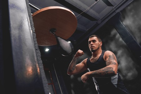 Born to win. Muscular tattooed athlete in sports clothing training hard on punching speed bag to become a champion, boxing gym interior Stock Photo