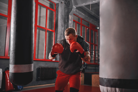 Impossible is Nothing. Muscular sportsman in sport clothing exercising on heavy punch bag before fight in boxing gym Stock Photo