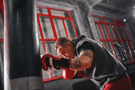 Keep climbing. Confident tattooed young boxer in red sports gloves training on heavy punch bag in boxing gym