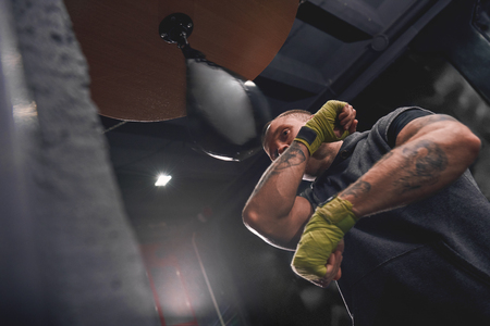 Lets get ready to rumble. Arm workout, professional young boxer with green hands wraps hitting punching speed bag in boxing gym
