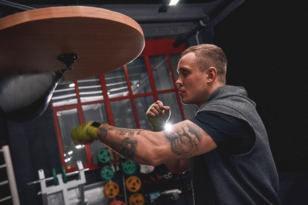 Stay strong to win. Side view of professional young boxer with green hands bandages hitting punching speed bag while training his boxing skills in boxing gym