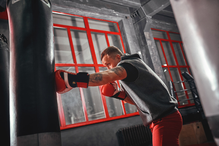 Be strong. Confident young boxer in red sports gloves training on heavy punch bag in boxing gym