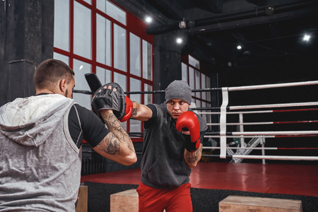 Nothing but success. Muscular athlete in red gloves training on boxing paws with partner in boxing gym Stock Photo