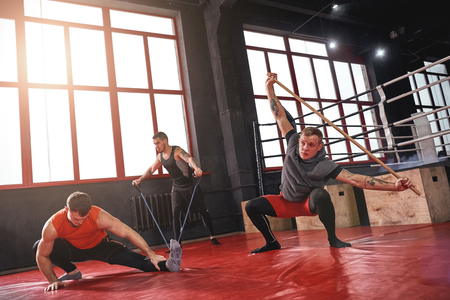 Stretch for success. Muscular young athletes in sports clothing stretching with sports equipment while warming up in boxing gym