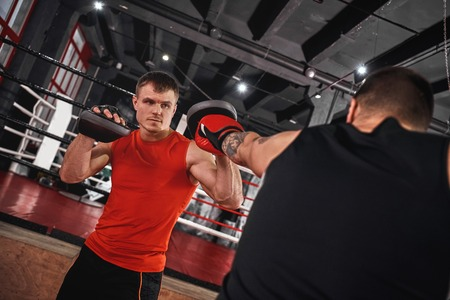 Power blow to boxing paw. Strong tattooed athlete in sports clothing training on boxing paws with partner opposite boxing ring Stock Photo