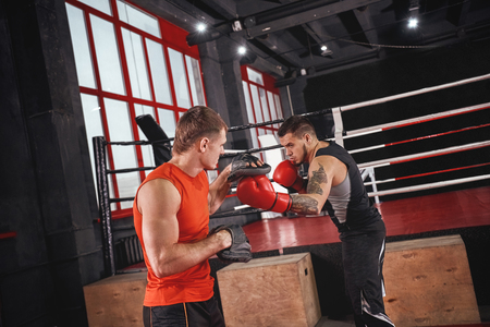Knockout punch. Strong tattooed athlete in sports clothing training on boxing paws with partner opposite boxing ring Stock Photo