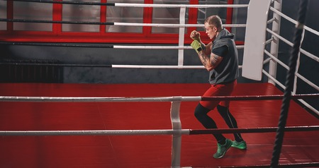 Training his boxing skills. Muscular tattooed boxer in sports clothing punching on red boxing ring while exercising in the gym