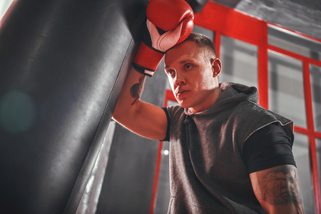 Taking time to rest. Tired young athlete in sports clothing taking break after hard training on heavy punch bag in boxing gym Stock Photo