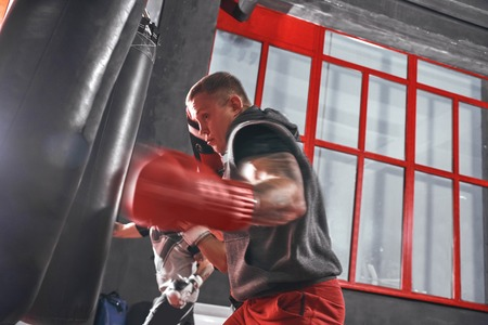 Ready to break his record. Young muscular athlete in sports clothing training hard on heavy punch bag before big fight in boxing gym
