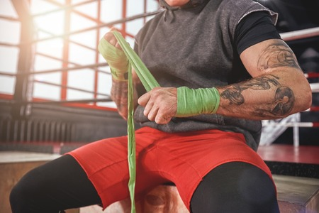 He is a new champion. Strong tattooed athlete in sports clothing wrapping hands with green boxing wraps, close-up of strong hands and fist ready for fight