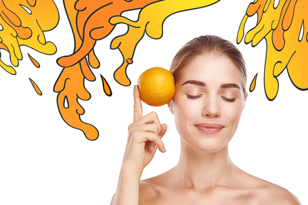 Vitamin C. Portrait of pretty and healthy woman with closed eyes holding an orange near her face while standing against white background with hand drawn orange splashes on it Stock fotó