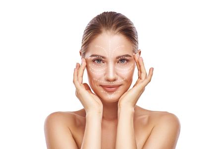 Massaggio viso antietà. Bella giovane donna con frecce bianche sul viso tenendo le mani sulla testa e guardando la fotocamera. Isolato su sfondo bianco. Cura della pelle. Linee di massaggio