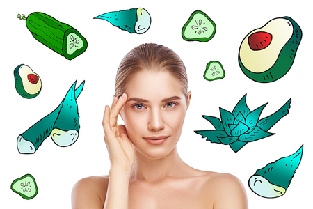 Face mask ingredients. Attractive young woman touching her clean and fresh skin and looking at camera while standing against background with colorful illustrations on it. Stock Photo