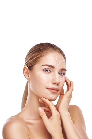 Visiting cosmetic clinic. Vertical photo of gorgeous woman touching her clean and healthy face with with lifting arrows on it. Isolated on white background. Face lifting concept