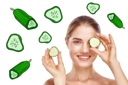 How to Make a Cucumber Facial Mask? Young beautiful woman hiding eye behind cucumber slice over while standing against white background with cucumber illustrations on it.