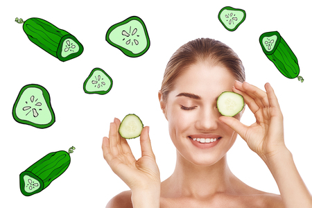 Natural Cucumber Face Mask. Young beautiful woman hiding eye behind cucumber slice over while standing against white background with cucumber illustrations on it.