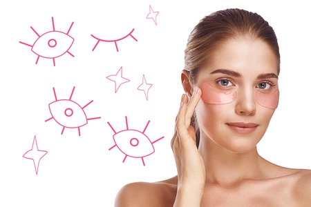 Beauty tips. Portrait of young and healthy woman with bare shoulders applying eye patches while standing against white background with hand drawn illustrations on in.