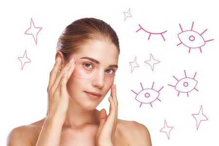 Eye Skin Care. Portrait of young and cute woman applying eye patches while standing against white background with hand drawn illustrations on in. Beauty and Spa concept Imagens