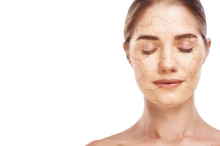 Effetto disidratazione. Ritratto di giovane donna attraente con gli occhi chiusi, viso screpolato e danneggiato su sfondo bianco. Concetto di cura della pelle.
