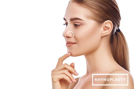 Nasenkorrektur - Nasenoperation. Seitenansicht einer attraktiven jungen Frau mit perfekter Haut und gepunkteten Linien auf ihrer Nase isoliert auf weißem Hintergrund. Konzept der plastischen Chirurgie Standard-Bild