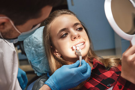 Stronger teeth for the future. Teen at the dental office. The dentist's explaining how to care for her teeth properly Stock Photo