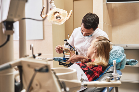 Start protecting your enamel. Teen at the dental office. The dentist's explaining how to brush teeth using the teeth model. Banque d'images - 120919480