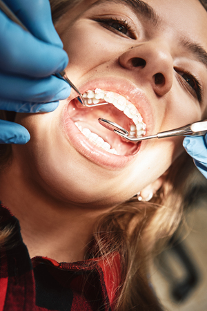 Your pathway to a bright new smile. Teen at the dental office. Dentist examining girls teeth in clinic.