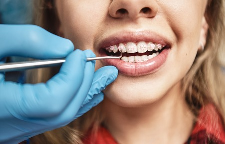Keep calm and smile. Teen at the dental office. Dentist examining girls teeth in clinic. Stock Photo