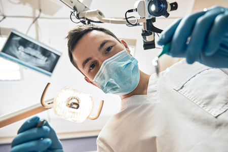 The experience you can count on. Young male dentist looks at teeth over open patients mouth. Inside view, stomatology concept. Low angle