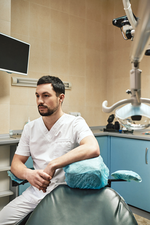 Dentistry for today's lifestyle. Young dentist looking away while sitting in his cabinet near dental chair